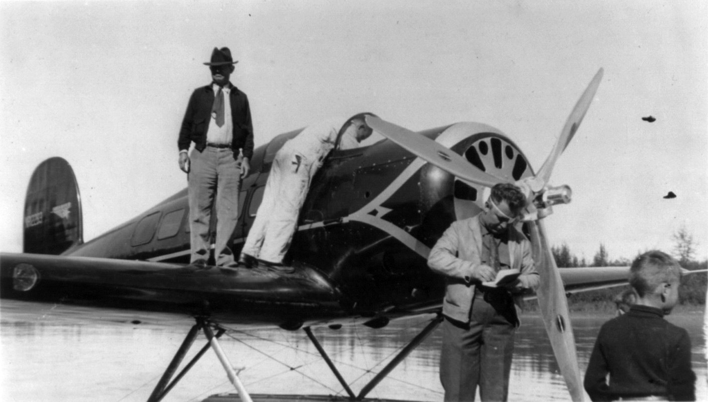 """Rogers standing on the wing of a seaplane, with Wiley Post standing in front of the propeller, August 1935"" Photo Credit Wiki"